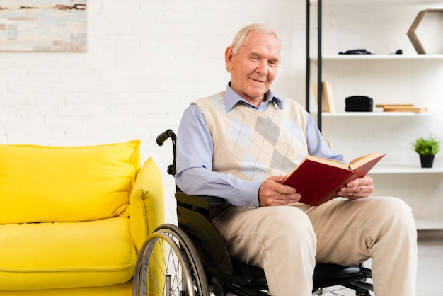 Old man sitting on wheelchair while reading book