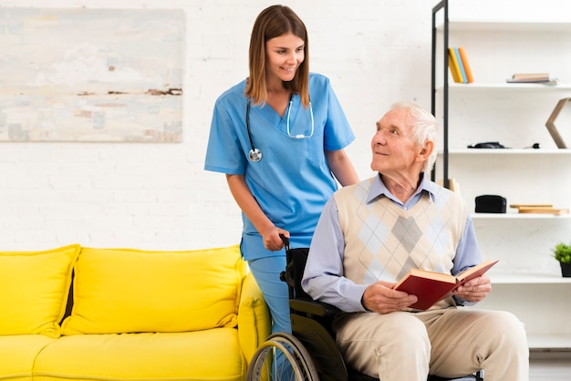 Old man sitting on wheelchair while talking to nurse