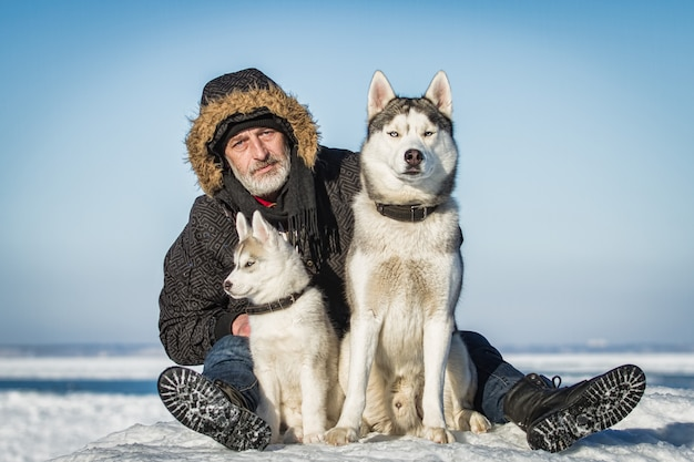 Old man and sled dogs on an ice floe.