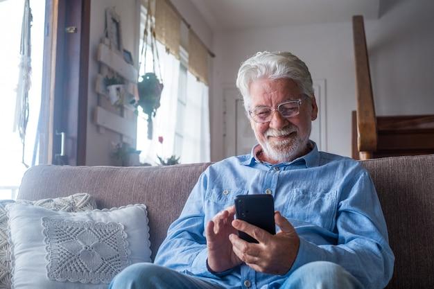 Старик улыбается, сидя на диване в гостиной, держа телефон, наслаждаясь использованием смартфона, чувствуя удовлетворение, отправляя сообщения, звоня друзьям, просматривая веб-концепцию онлайн