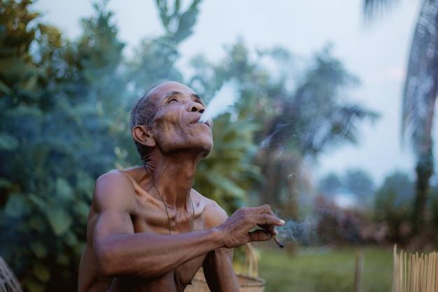 Old man smokes cigarettes.