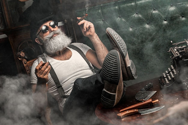 Старик курит сигару в помещении. концепция мафии стильный мужчина в своем кабинете. бородатый мужчина.