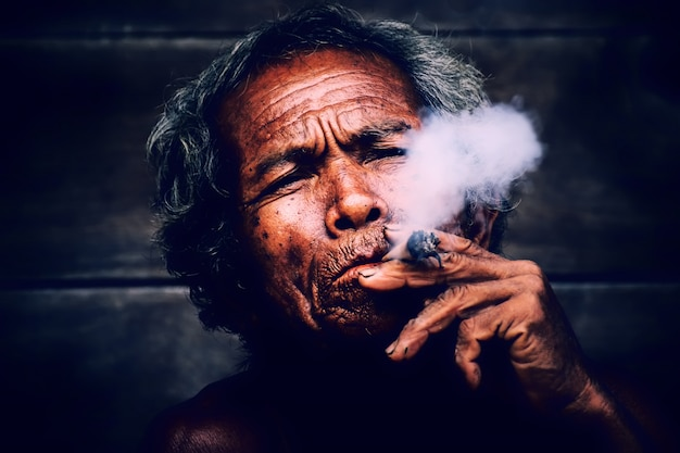 Old man smoking cigarette or tobacco .