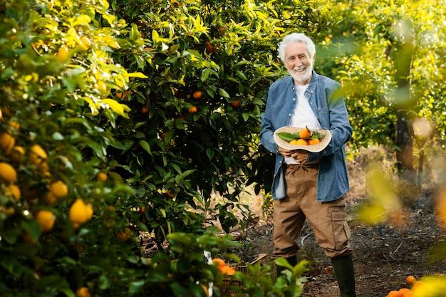 Il vecchio uomo in piedi accanto ai suoi alberi di arancio all'aperto