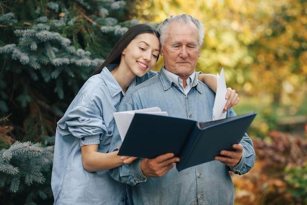 Старик стоит в парке с внучкой