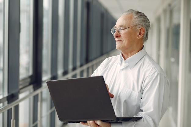 Старик стоит в офисе с ноутбуком