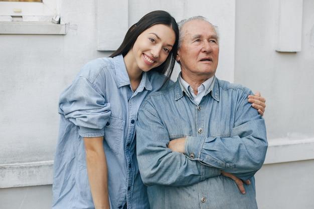 彼の孫娘と灰色の背景に立っている老人