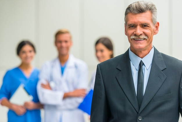An old man stands and smiles in hospital or clinic