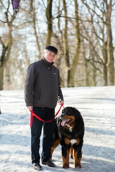 Old man stands with bernese mountain dog on the snow in park