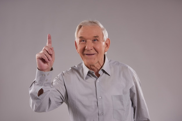 Old man stands with indexed finger up on gray.
