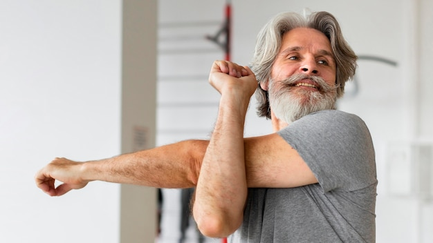 Old man stretching indoors