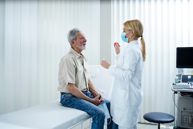 Старик берет мазок из носа или горла, чтобы пройти тест на вирус короны.