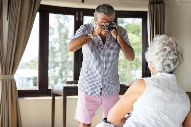 Old man taking a photo of his wife