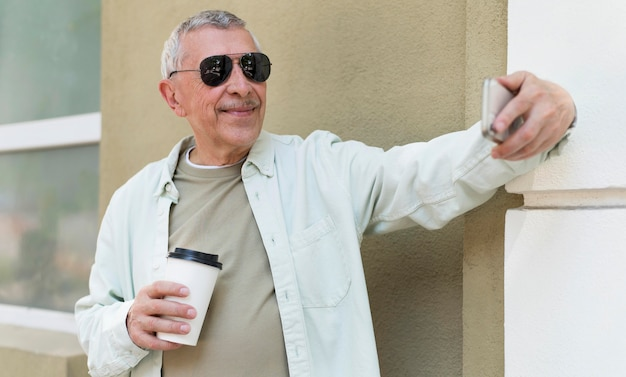 Old man taking selfie with phone