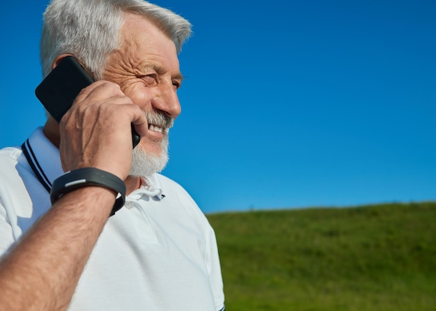 Old man talking on cell phone in the field.