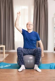 居間で安定ボールに座って腕を訓練する老人