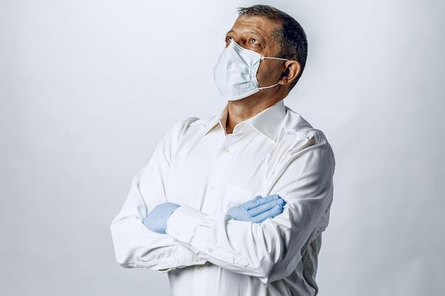 보호 마스크와 장갑을 착용하는 노인을 닫습니다.