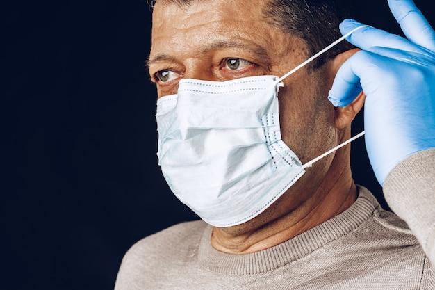 어두운 벽에 보호 마스크와 장갑을 착용하는 노인. 확대.