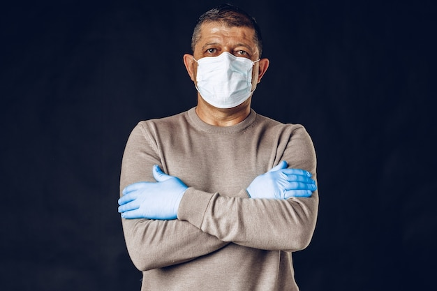 Old man wearing protective mask and gloves on dark wall. close up.
