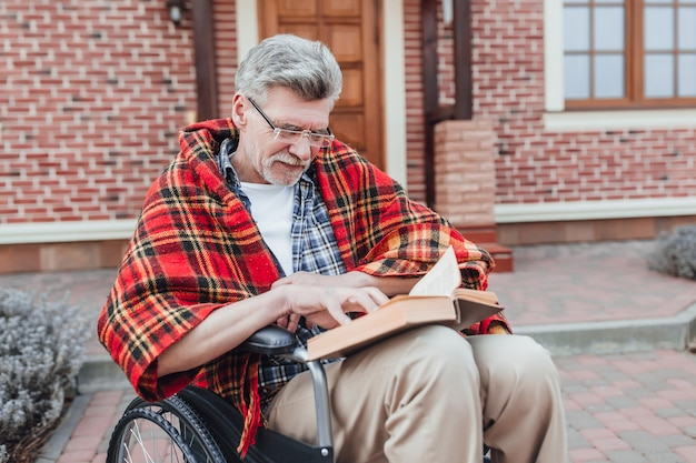 Old man on wheelchair reading interesting novel and posing to the camera near nursing home
