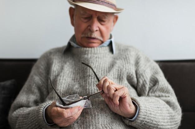 Il vecchio si pulisce gli occhiali in una casa di cura