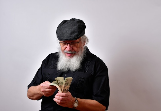 An old man with a beard counting his money