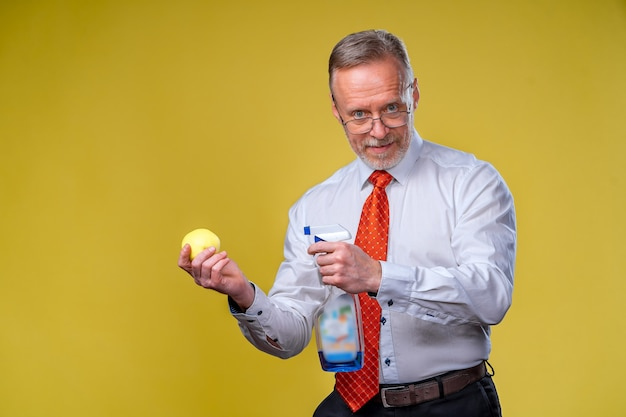An old man with a beard holds out a yellow apple. isolated on yellow background.