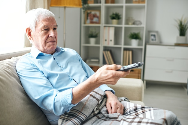 체크 무늬 격자 무늬가 소파에 앉아 집에서 tv를 보면서 리모콘 버튼을 누른 노인