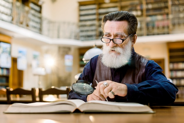 Old man with gray beard, in glasses, vintage clothes, reading a book in the ancient library, using magnifying glass
