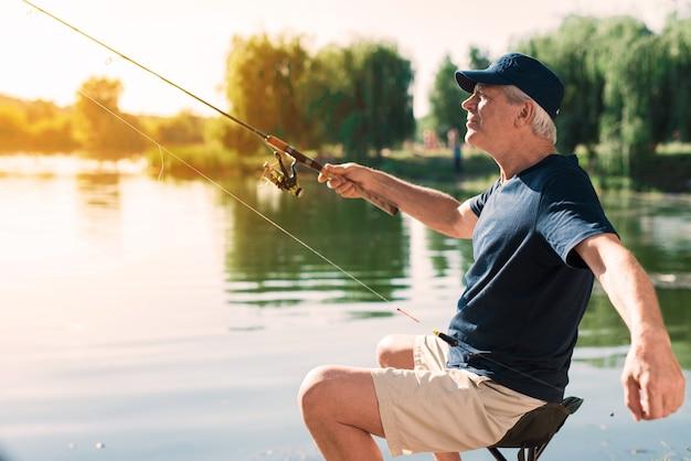 Старик с седыми волосами, рыбалка на реке летом.