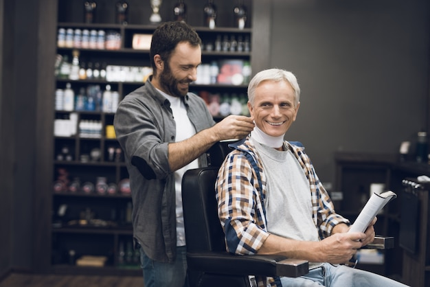 Old man with gray hair sits in stylist in barbershop.