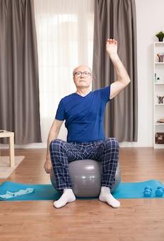 Uomo anziano con uno stile di vita sano che si allena in soggiorno