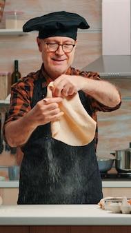 カメラの前で微笑んで家でパン生地で遊んでキッチンエプロンを持つ老人。引退した年配のシェフが、モダンなキッチンで、粉にされた表面にピザのカウンタートップを形成し、それを手でこねます