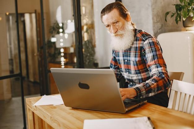Uomo anziano con il computer portatile. nonno seduto in un addobbo natalizio. uomo in camicia di cella.