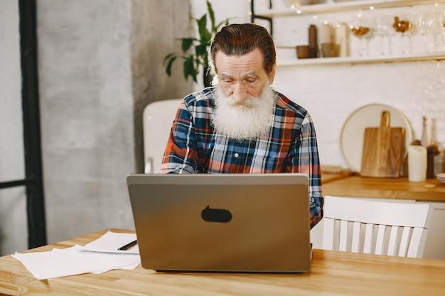 Старик с ноутбуком. дед сидит в рождественских украшениях. мужчина в клетчатой рубашке.