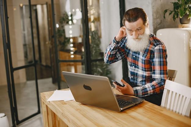 Старик с ноутбуком. дед сидит в рождественских украшениях. человек с мобильным телефоном.