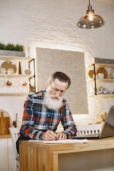 ラップトップを持つ老人。クリスマスの飾りに座っている祖父。