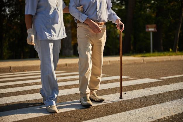 도시의 횡단보도를 걷고 있는 의료 종사자와 노인