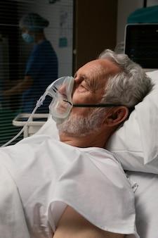 Vecchio con respiratore in un letto d'ospedale