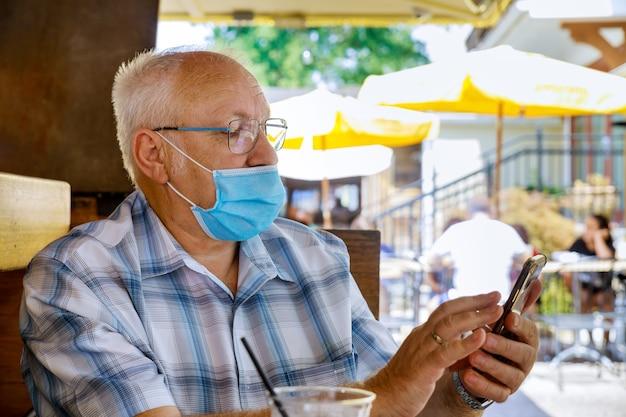 スマートフォンを使用している老人、公園でコロナウイルスcovid-19中に医療用マスクを身に着けている白い保護