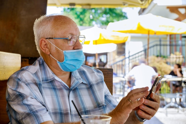 Old man with using smartphone, white a wearing medical mask protect during coronavirus covid-19 in a park