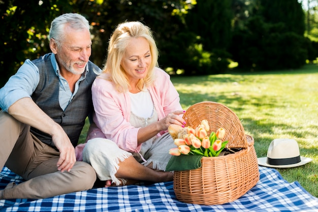 Old man and woman looking at the picnic basket