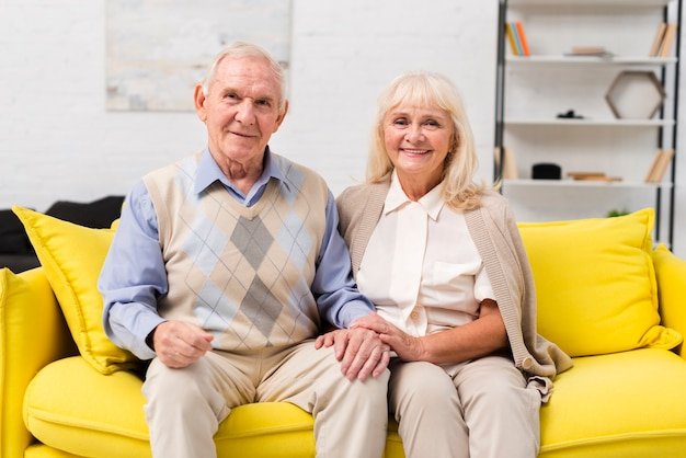 Old man and woman sitting on yellow sofa