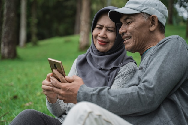 Old man and woman using mobile phone in the park