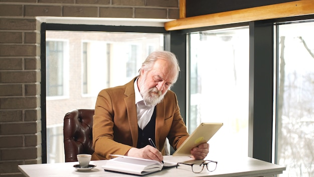 Old man working on a digital tablet in home office