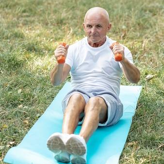 Старик работает на коврик для йоги