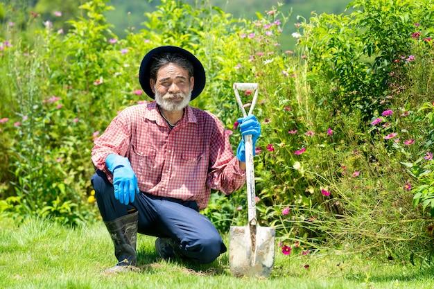Old man working with shovel in backyard garden.