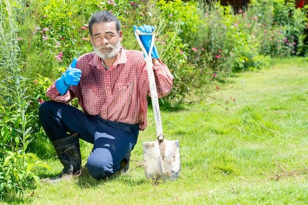 Старик работая с лопаткоулавливателем в саде задворк.