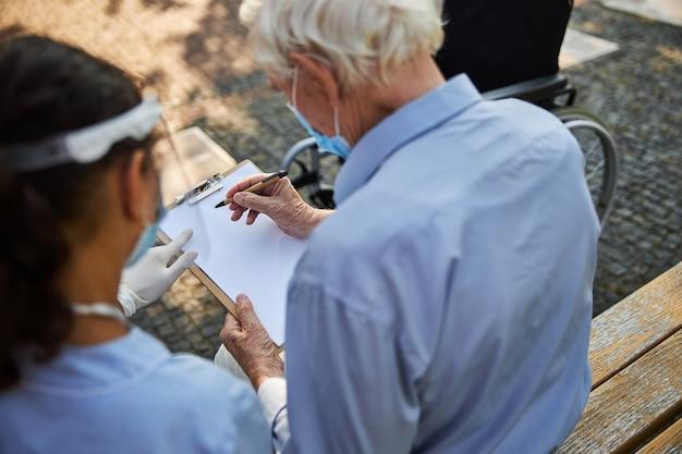 看護師の近くのベンチに座っている間彼のファイルに書いている老人