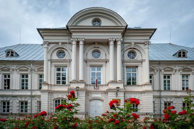 手前に赤いバラのある古いマナーハウス。 zalenieki manor、green manor、ラトビア。